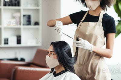 Hairdresser and customer in salon with medical masks during pandemic