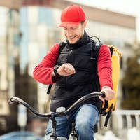 Happy Courier Checking Time On Wristwatch Sitting On Bike Outdoor