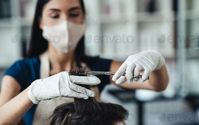Hairdresser in medical mask cutting hair of male customer, close up