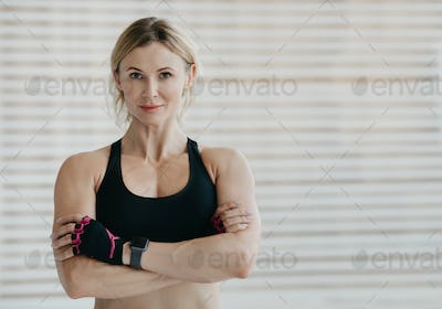 Fitness model and motivation. Friendly woman with smart watch with arms crossed, demonstrates