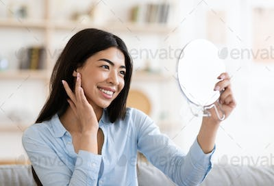Natural Beauty. Asian girl holding magnifying mirror and touching her perfect skin
