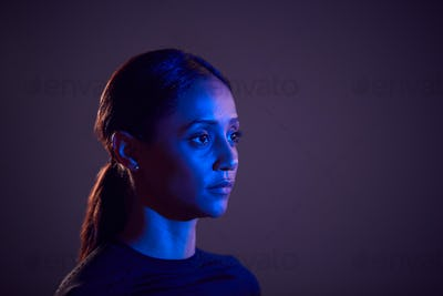 Studio Profile Shot Of Woman With Face Illuminated By Blue Light