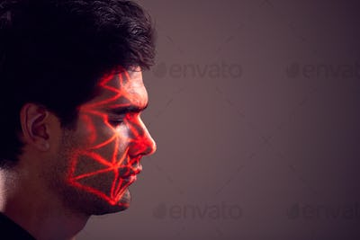 Facial Recognition Technology Concept As Man Has Red Grid Projected Onto Face In Studio