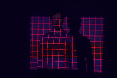 Facial Recognition Technology Concept As Man Has Red Grid Projected Onto Body In Studio