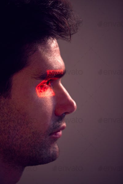 Facial Recognition Technology Concept As Man Has Red Grid Projected Onto Eye In Studio