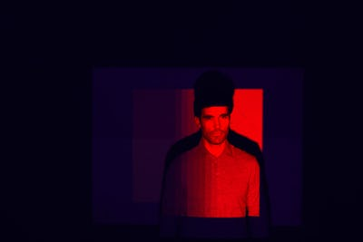 Studio Shot Of Man With Face Illuminated By Red Light
