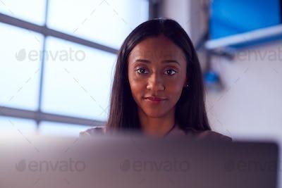 Businesswoman Working On Laptop At Desk In Modern Office