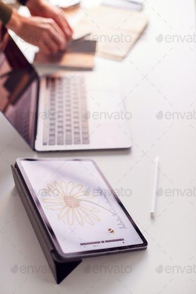 Close Up Of Desk Of Graphic Designer With Image Drawn On Digital Tablet
