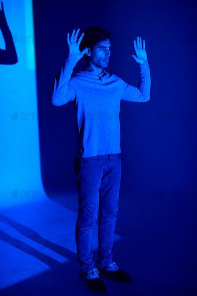 Studio Shot Of Man With Body Illuminated By Blue Light