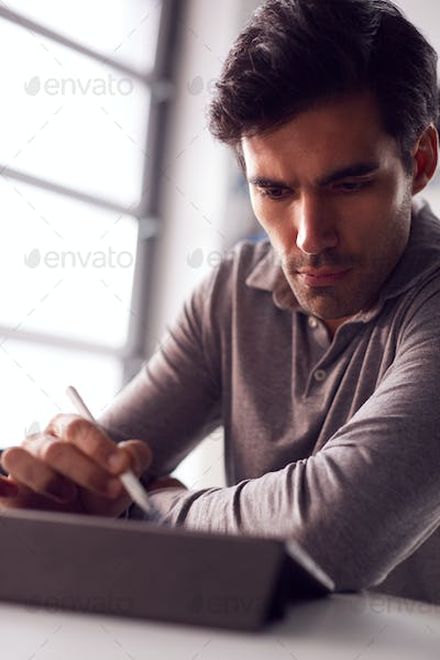 Businessman Working From Home Drawing On Digital Tablet Using Stylus Pen