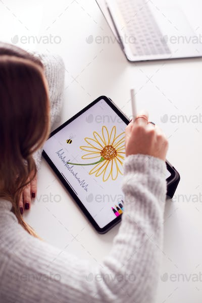 Overhead View Of Businesswoman Working From Home Drawing On Digital Tablet Using Stylus Pen