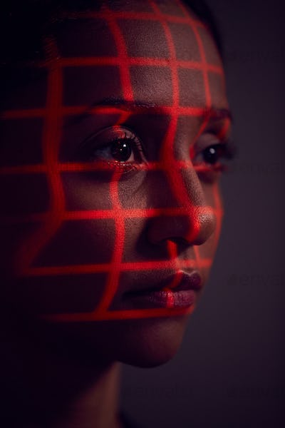 Facial Recognition Technology Concept As Woman Has Red Grid Projected Onto Face In Studio