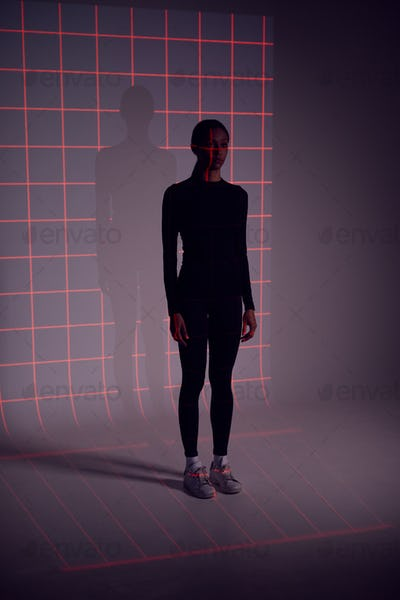 Facial Recognition Technology Concept As Woman Has Red Grid Projected Onto Body In Studio