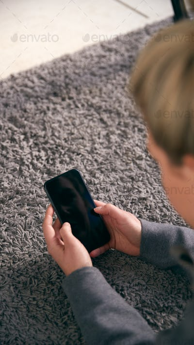 Overhead Shot Of Woman Looking At Screen With Copy Space On Mobile Phone Lying On Carpet