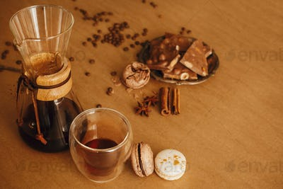 Glass cup with fresh coffee, roasted beans, grounded coffee on spoon, glass flask for filter coffee