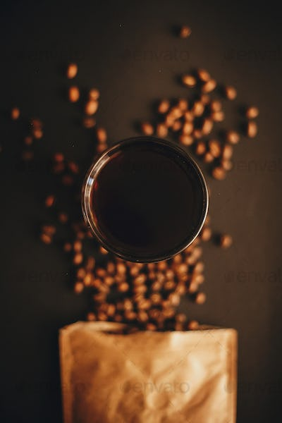 Coffee in glass cup and coffee beans scattered from paper pack on black background