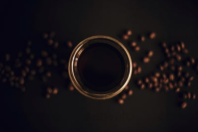 Fresh coffee in glass cup with coffee beans on black background flat lay