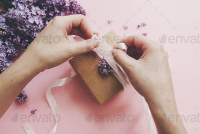 Hands wrapping gift box with ribbon and lilac flowers on pink paper
