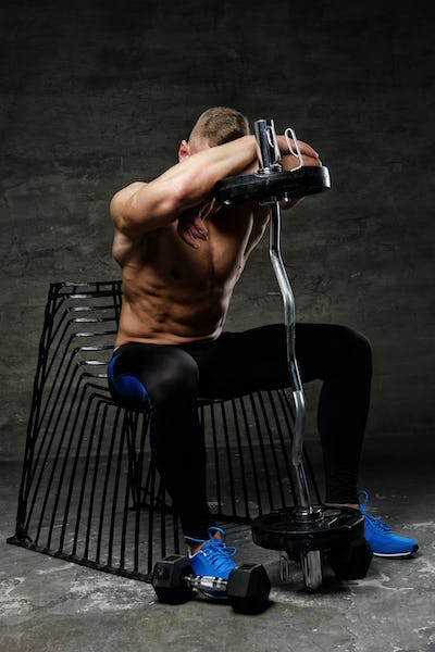 A man posing in studio with barbell.