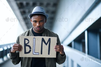 Man with BLM sign standing outdoors, black lives matter concept