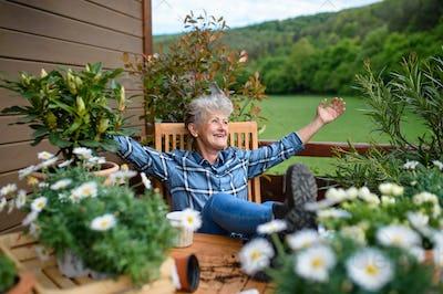 Senior grandmother gardening on balcony in summer, resting