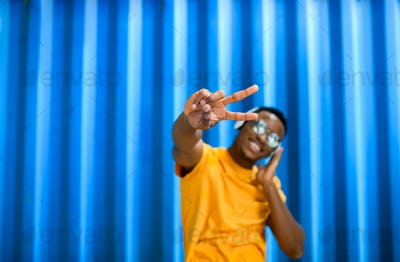Cheerful young black man standing against blue background, peace gesture concept