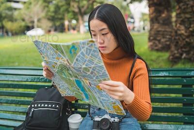 Asian woman looking at a map.