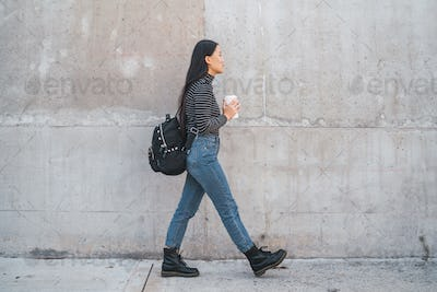 Asian woman walking and holding a cup of coffee.