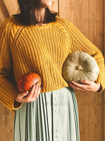 Hipster girl in yellow sweater holding pumpkins on rustic wooden background