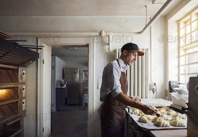 Baker preparing croissants in kitchen
