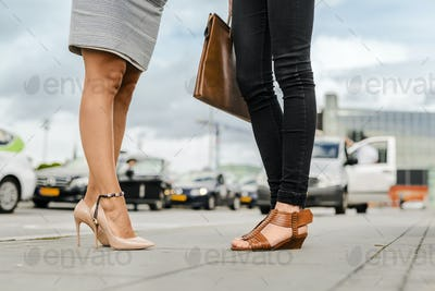 Low section of two women in city street