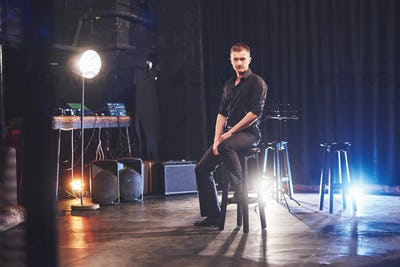 Handsome young man in black clothes looking at camera while sitting on chair near the in dark room