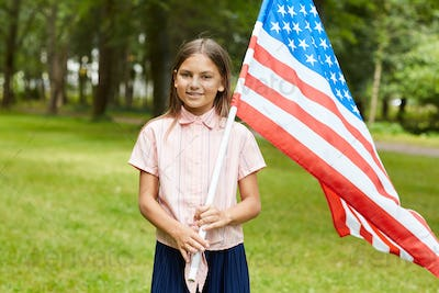 Portrait of Cute Girl Holding American Flag Outdoors