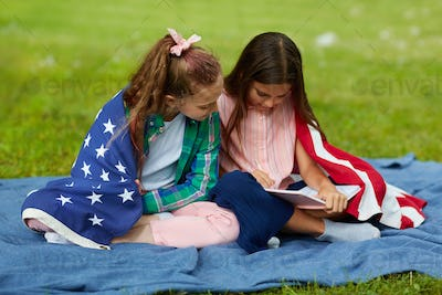 Two Girls Sitting on Green Grass in Park