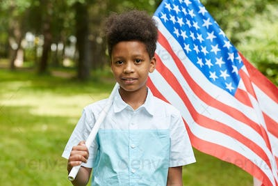 Smiling African Boy Holding American Flag Outdoors