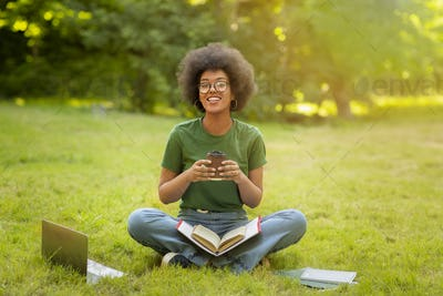 Black student girl resting at college campus, sitting on lawn with coffee