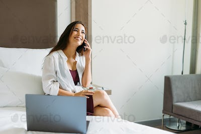 Beautiful smiling asian girl with long hair speaking on mobile with laptop on bed in the hotel room