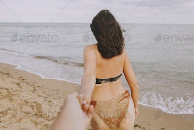 Woman leading her man, holding hands on beach
