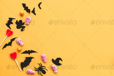 Halloween candy, skulls, black bats and ghost paper decorations