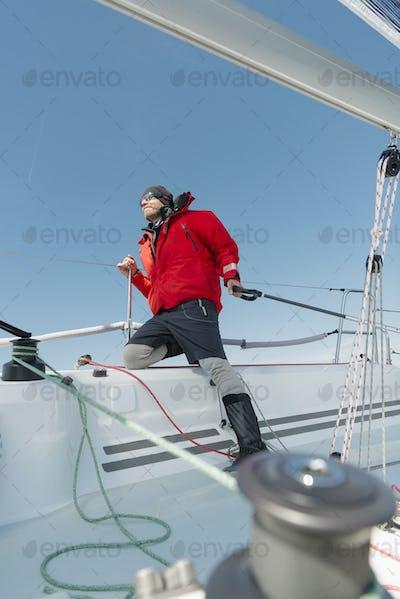 Man navigating sailboat