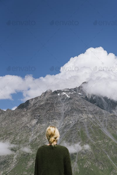 Rear view of woman looking at mountain covered with clouds