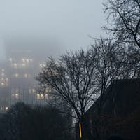 Apartment building covered with clouds and fog at dusk