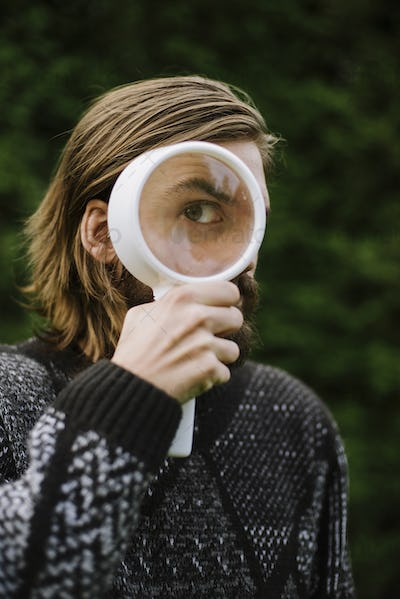 Portrait of man holding magnifying glass in front of eye