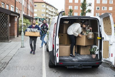 Man and women putting furniture into rental car