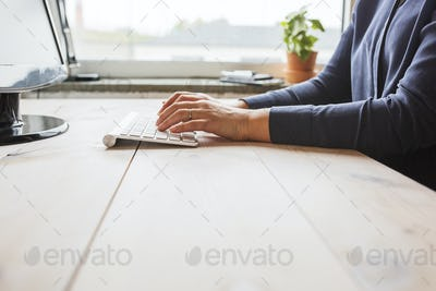 Woman using computer on wooden table