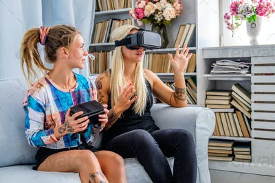 Two females having fun with virtual reality glasses.