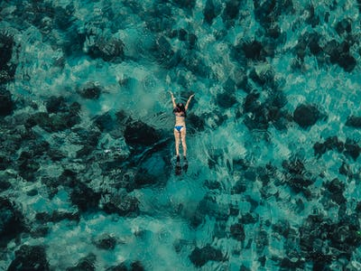 Aerial View of Girl Swimming On The Sea