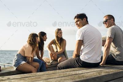 Friends sitting by sea