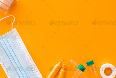 Flat lay of several medical supplies against a yellow background