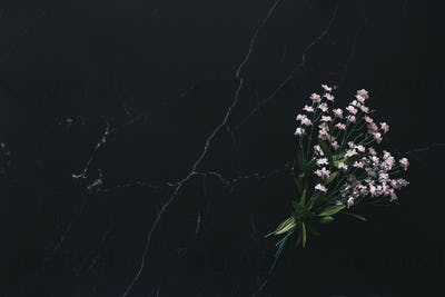 Flat lay of a floral arrangement against black marble